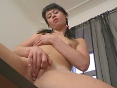 Brunette with ponytails massages her clitoris on the table