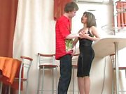 Horny brunette mom surprises a young stud with a hot fuck in the kitchen