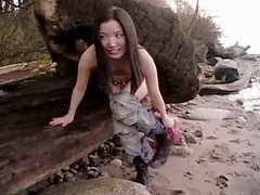 Young asian cutie gets naked at the beach