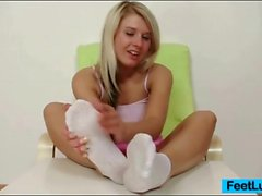 Blonde teen girl gives a dildo footjob in close up