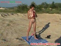 Teen on the beach licks a giant dildo