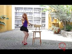 Brazilian model dancing and stripping around the chair